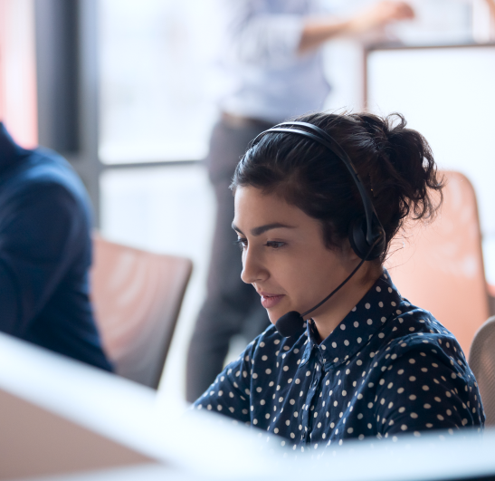 woman sitting at a desk wearing a headset